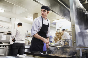 Male chef student tossing meat with colleagues in background at cooking school
