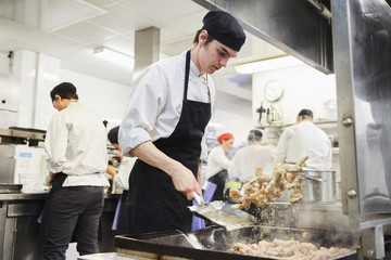 Male chef student tossing food with teacher and colleagues in background at cooking school