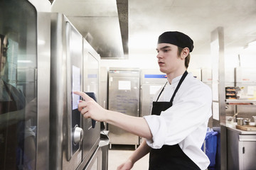 Male chef student operating microwave oven at cooking school