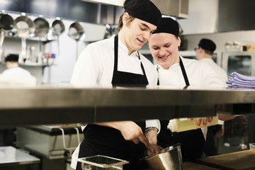 Young male chefs cooking together in commercial kitchen