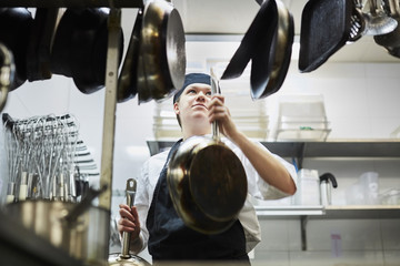 Low angle view of chef arranging frying pan in commercial kitchen