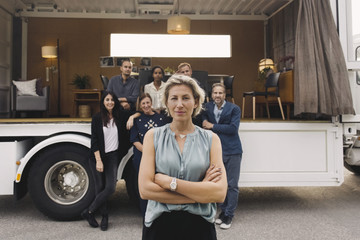 Portrait of confident businesswoman with team and portable office truck in background