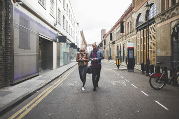 Full length of multi-ethnic couple walking on city street