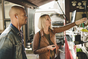 Mid adult man with woman buying coffee at food cart
