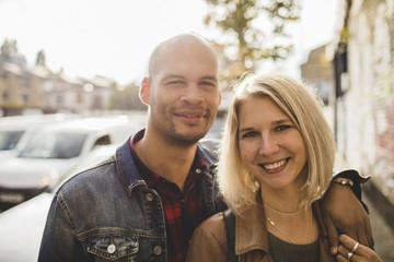 Portrait of loving couple smiling on sidewalk in city