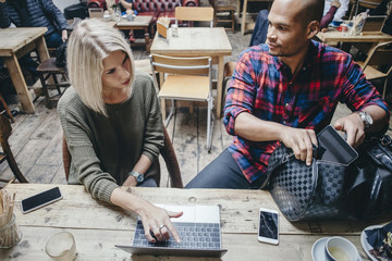 Woman using laptop while discussing with man in coffee shop