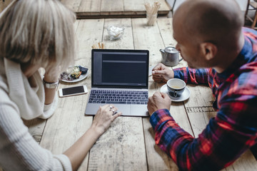 Multi-ethnic couple using laptop at table in coffee shop