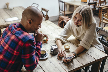 Multi-ethnic couple using mobile phone at table in coffee shop