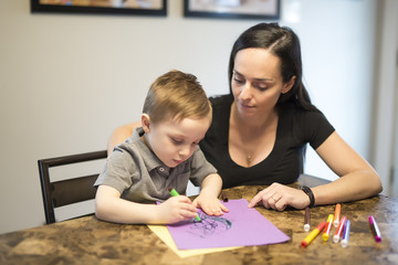 Child drawing with his mom, sitting at table in kitchen at home