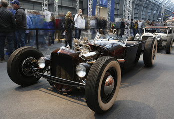 Visitors walk past a hot rod car based on a vintage Ford at the Essen Motor Show in Essen