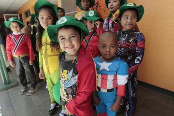 Child cancer patients dressed as superheroes poses for pictures after a march in Managua