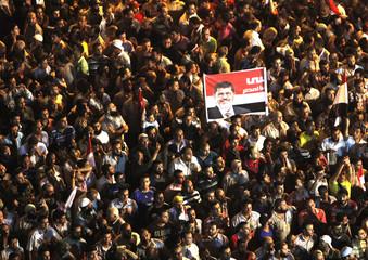 Supporters of Muslim Brotherhood's presidential candidate Morsy hold up a poster of Morsy during a demonstration at Tahrir square in Cairo