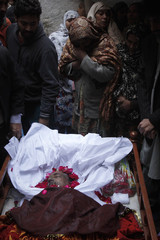 Neighbors view the body of 62-year-old heart patient Chaudhry Mohammad Gulab before his burial in Lahore