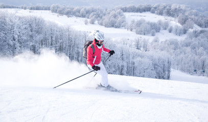 Woman skier skiing on mountain slope
