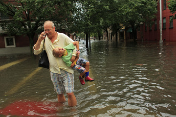 A man carries his son in a flooded street after the pass of Hurricane Irene at Hoboken in New Jersey