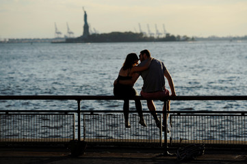 A couple kiss as they watch the sunset silhouette the Statue of Liberty from Battery Park in New York