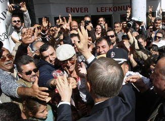 "U.N. Secretary-General Ban Ki-Moon waves to Turkish Cypriots after passing Ledra Street, which runs across a United Nations-controlled ""green line"" splitting Nicosia, the ethnically-split capital of Cyprus"