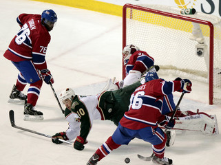 Minnesota Wild Setoguchi trips over Canadiens goalie Price as Canadiens Gorges and Subban pick up loose puck during first period NHL hockey action in Montreal