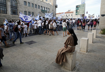 A nun watches as people wave Israeli flags during a parade marking Jerusalem Day, in Jerusalem