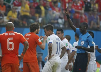 Blind of the Netherlands receives a yellow card by referee Gassama of Gambia during their 2014 World Cup Group B soccer match against Chile at the Corinthians arena in Sao Paulo