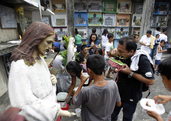 Families share meals as they visit tombs of deceased relatives during the commemoration of All Saints Day in Navotas City