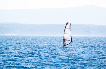 Windsurfer surfing on blue sea