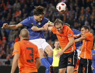 Sweden's Ibrahimovic heads the ball past Netherland's Mathijsen and Van der Wiel as Heitinga looks on during their Euro 2012 qualifying soccer match in Amsterdam