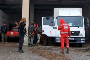 Rebel fighters inspect Red Crescent vehicles on their way to al Foua and Kefraya, in Idlib province, Syria