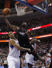 Miami Heat's Wade goes to the basket past Philadelphia 76ers' Turner and Brand during their NBA basketball game in Philadelphia
