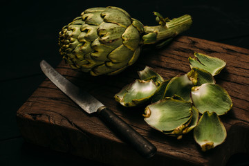 Close up of artichoke and knife on wooden table against black background