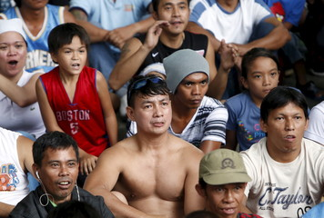 Fans of boxing icon Manny Pacquiao react as they watch his fight with Floyd Mayweather Jr. at a public park in Marikina city