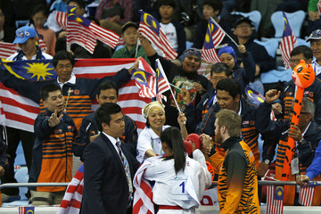 Malaysia's Syakilla Salni Binti Jefry Krisnan talks with supporters after defeating Uzbekistan's Barno Mirzaeva in the women's -61kg final contest of the karate competition at Gyeyang Gymnasium during the 17th Asian Games in Incheon