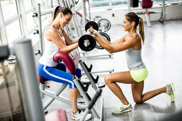 Pretty young women have weight training in the gym