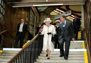 Britain's Queen Elizabeth speaks with the managing director of London Underground during her visit to Baker Street underground station in London