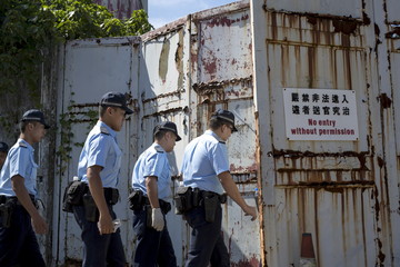 Policemen search for evidence after finding explosives at an abandoned former ATV studio in Hong Kong, China