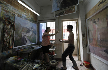 Painters joke as they work in a studio at Dafen Oil Painting Village in Shenzhen