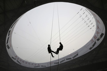 Two cleaners are seen attached to ropes at the top of the National Stadium, also known as the Bird's Nest, on a hazy day in Beijing