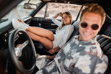 Happy young couple sitting in the car