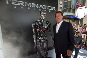 "Cast member Schwarzenegger poses by a Terminator replica at the premiere of ""Terminator Genisys"" in Hollywood"