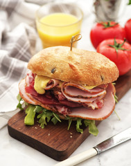 Sandwich with ham and fresh salad and tomatoes served on a wooden board.