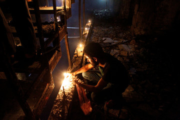 A man lights a candle at the site after a suicide bombing in the Karrada shopping area, in Baghdad, Iraq