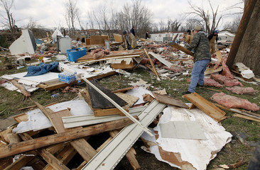 Residents look through their storm-damaged homes for their belongs in Henryville