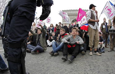 Demonstrators sit in near the Arc de Triomphe during a protest march over France's planned legalisation of same-sex marriage, in Paris