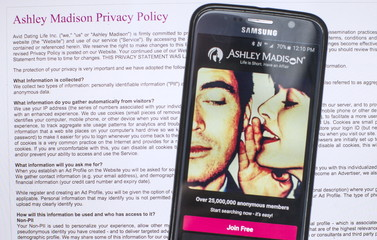 A photo illustration shows the privacy policy of the Ashley Madison website seen behind a smartphone running the Ashley Madison app in Toronto