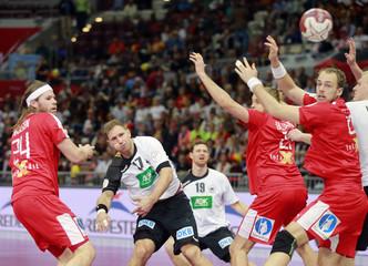 Weinhold of Germany attempts to score past Mikkel Hansen, Mollgaard and Henrik Toft Hansen of Denmark during their preliminary round of the 24th men's handball World Championship in Doha