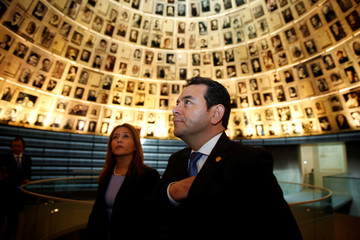 Guatemalan President Jimmy Morales and his wife Hilda Patricia Marroquin look at pictures of Jews killed in the Holocaust during a visit to the Hall of Names at Yad Vashem's Holocaust History Museum in Jerusalem