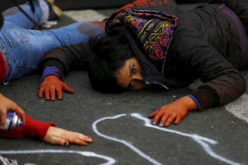 A demonstrator lies on the floor pretending to be dead, in reference to a student shot dead on May 14 after a protest march, during a rally, as Chile's President Michelle Bachelet delivers a speech inside the National Congress, in Valparaiso city