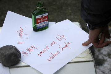 Message written by Chinese Google user Huang is seen next to bottle of wine in front of the Google China headquarters in Beijing