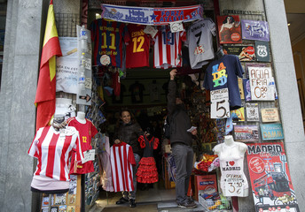 People look at Real Madrid and Atletico Madrid merchandise inside a souvenir shop in central Madrid