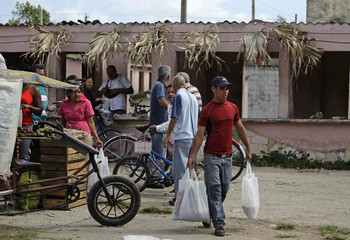 Luis Salgado carries goods he bought near their home in the village of Sagua La Grande